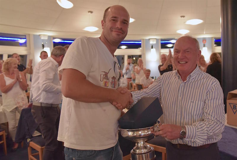 Deilginis helm Luke Massey is presented the Howth 17 trophy by Class Captain (and Handicap winner) Tom Houlihan.