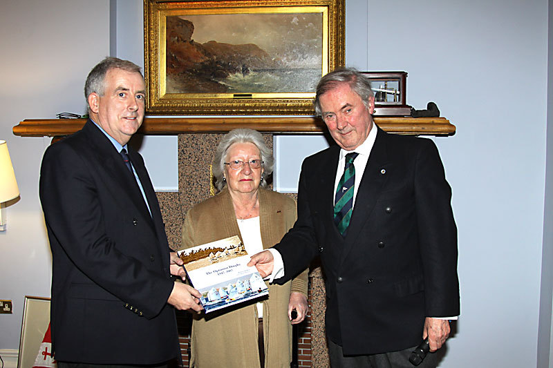 The Commodore is presented with 'The Optimist Dinghy' by Helen Mary and author Robert Wilkes
