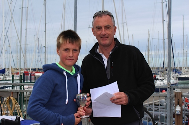 Rear Commodore Richard Kissane presents Jamie McMahon with his prize for 1st place in the Optimist Main Fleet