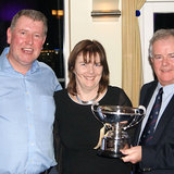 Therese Bermingham (Bite the Bullet) is presented the 'Kumquat Cup' by Fergal Noonan and Commodore Berchmans Gannon
